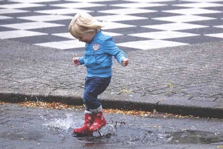 ילד קופץ בתוך שלולית