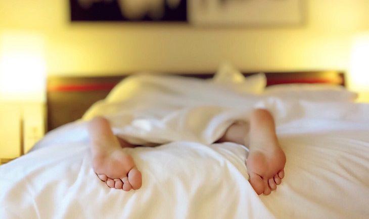 תמונה של כפות רגליים של אדם ששוכב על הבטן במיטה