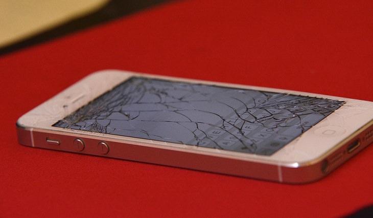 טלפון עם מסך שבור שוכב על שולחן