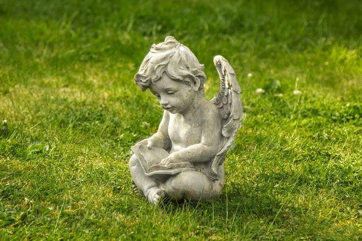 פסל של ילד מלאך קורא ספר