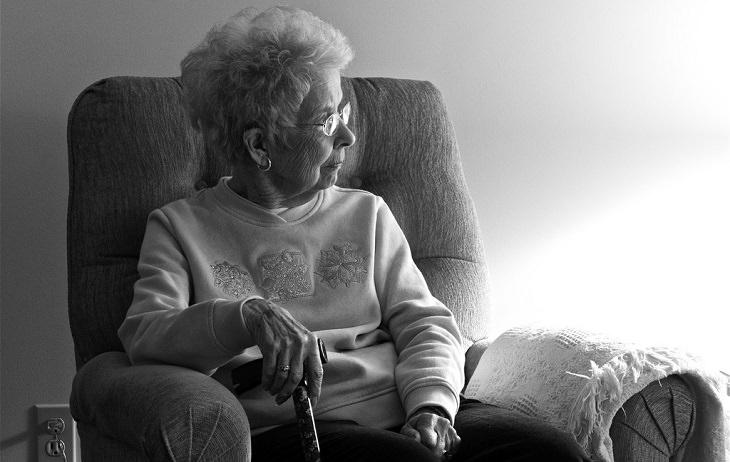 אישה מבוגרת יושבת על כסא