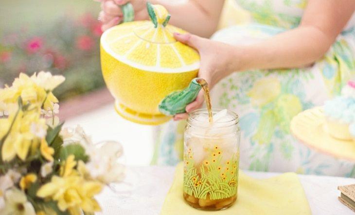 יד מחזיקה קנקן עם ציור של לימון ומוזגת לימונדה לכוס