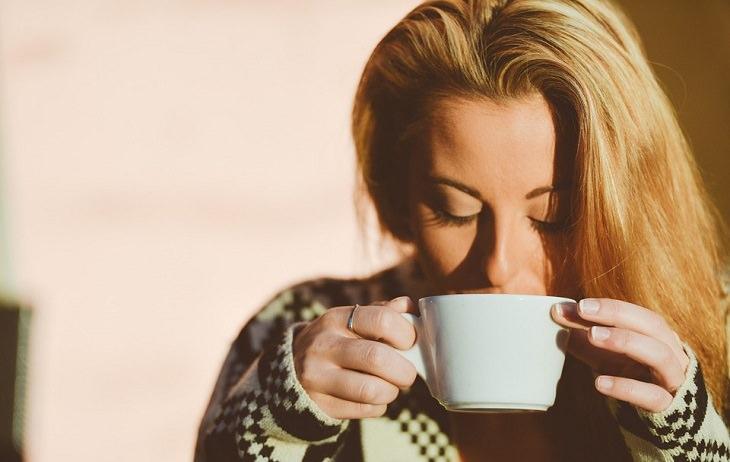 אישה מחזיקה ספל ולוגמת משקה