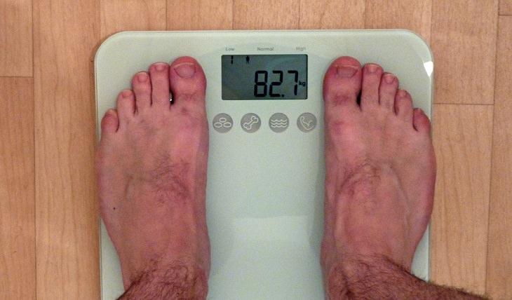 גבר עומד על המשקל