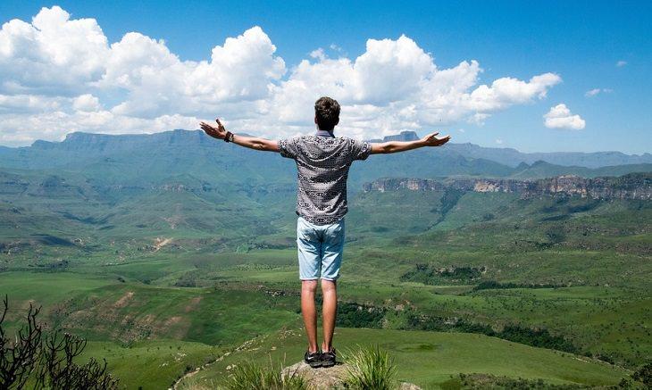 איש צעיר עומד ומסתכל אל עבר האופק עם ידיים מורמות