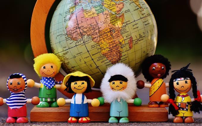 בובות עץ של אנשים ממדינות שונות מול גלובוס