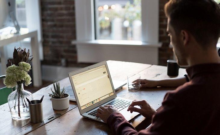 אדם יושב מול שולחן משרדי עם מחשב נייד