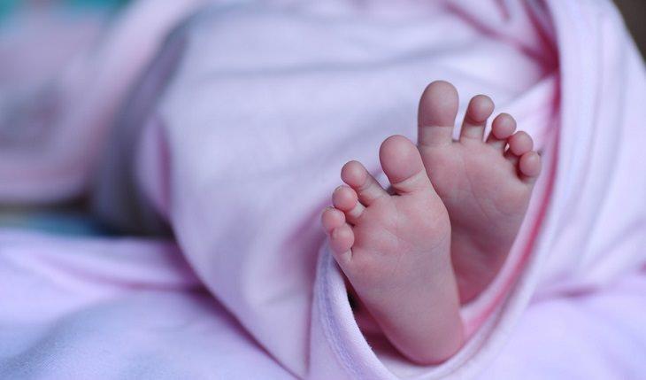 רגליים של תינוק שוכב על הגב