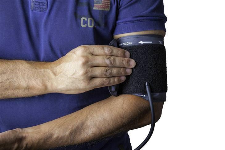 אדם אוחז בשרוול לחץ דם שמולבש על זרועו