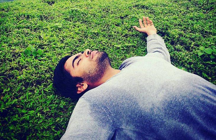 אדם שוכב על הדשא עם ידיים לצדדים כשהוא עוצם את עיניו