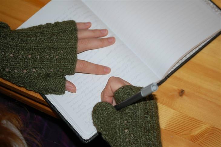 ידיים של אישה לבושה בסוודר שכותבת במחברת