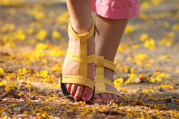 רגליים של אישה בסנדלים הולכות על אדמה שמכוסה בשלכת פרחונית