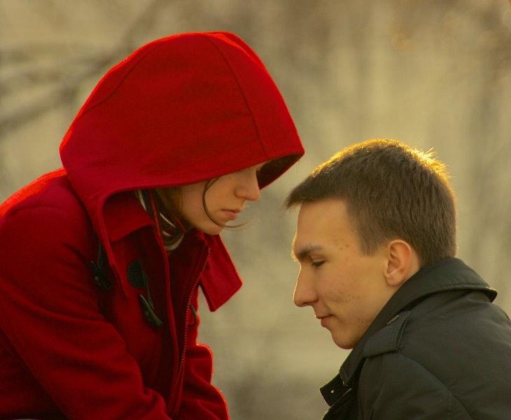 אישה מתכופפת מול גבר שמסתכל למטה ולא על העיניים שלה