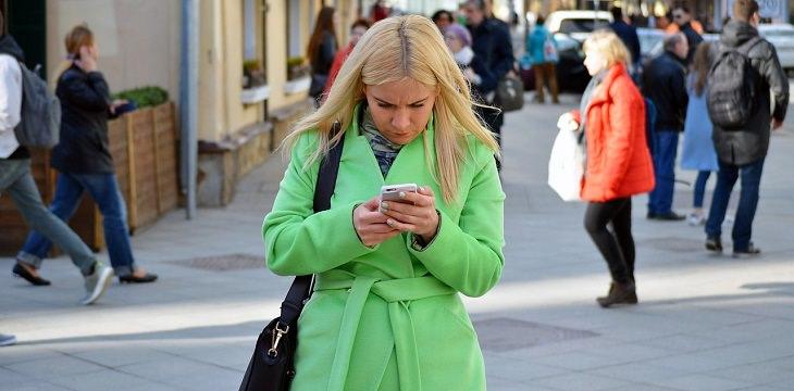 אישה מסתכלת בטלפון ברחוב