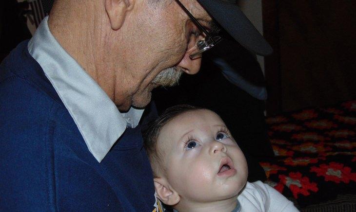 איש מבוגר מסתכל על נכדו התינוק