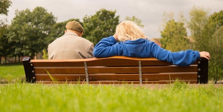 איש מבוגר יושב ליד אישה צעירה יותר על ספסל