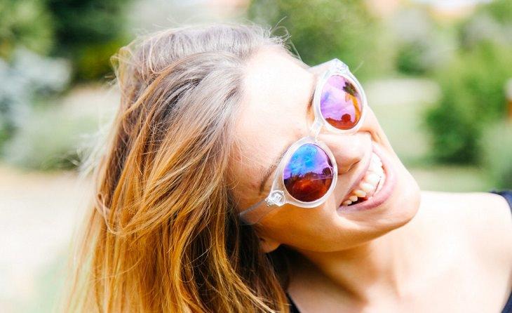אישה מחייכת  עם משקפי שמש