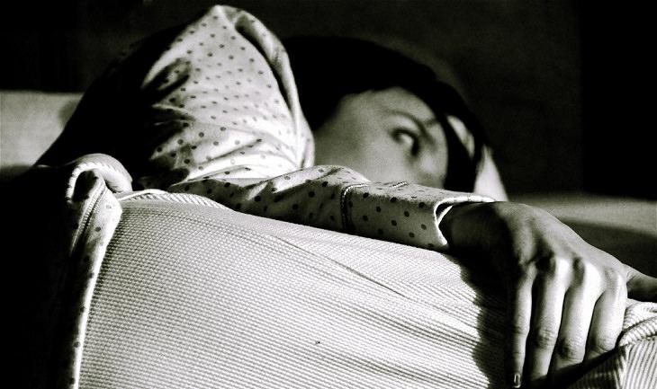 אישה שוכבת במיטה ערה