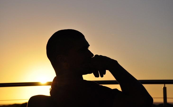 צללית של אדם יושב וחושב כשהוא מניח את ידו על אזור הסנטר
