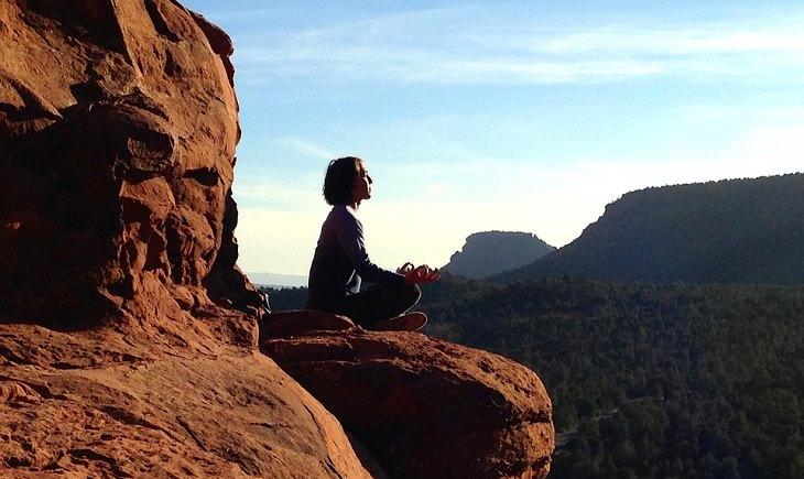 אישה יושבת ומתרגלת מדיטציה על צוק של הר