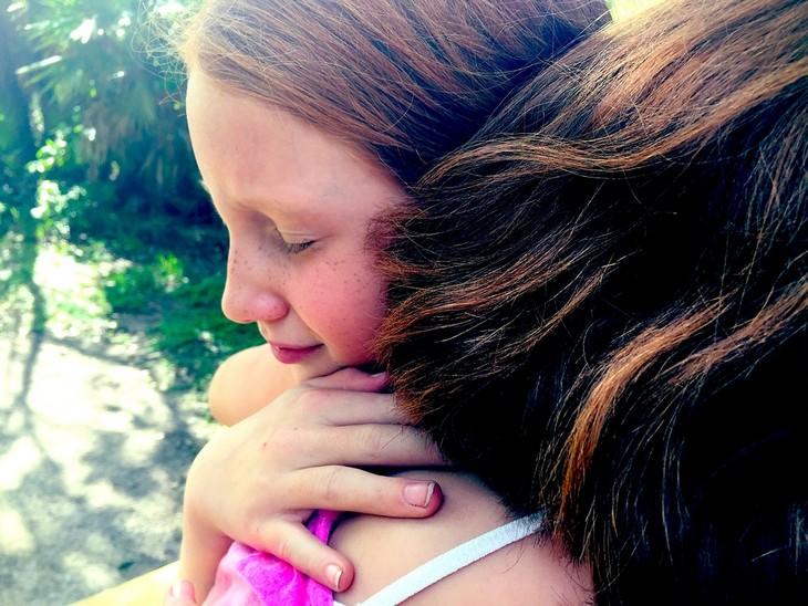 ילדה ואמא מתחבקות