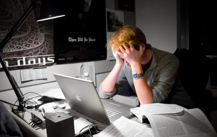 עובד יושב מול שולחן עבודה ומחזיק את הראש עם הידיים