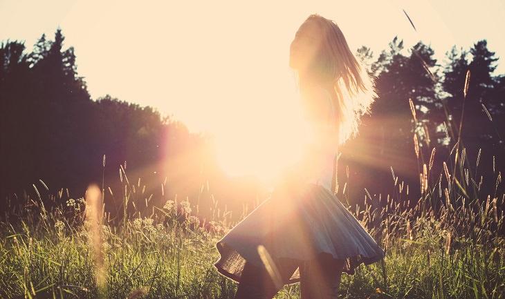 אישה עומדת בפרדס ומסנוורת מהשמש