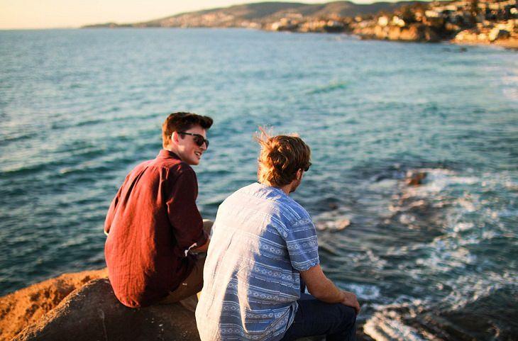 שני חברים יושבים על סלע מול הים ומשוחחים