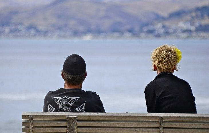 זוג יושבים על ספסל רחוקים אחד מן השנייה