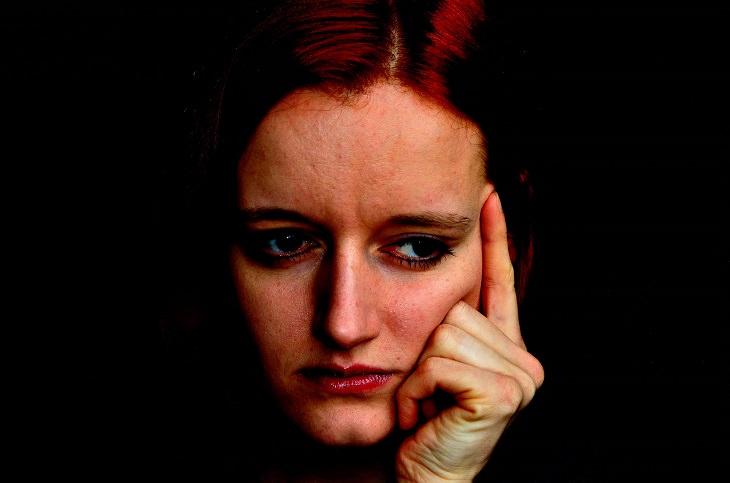 אישה מדוכדכת ושעונה על ידה