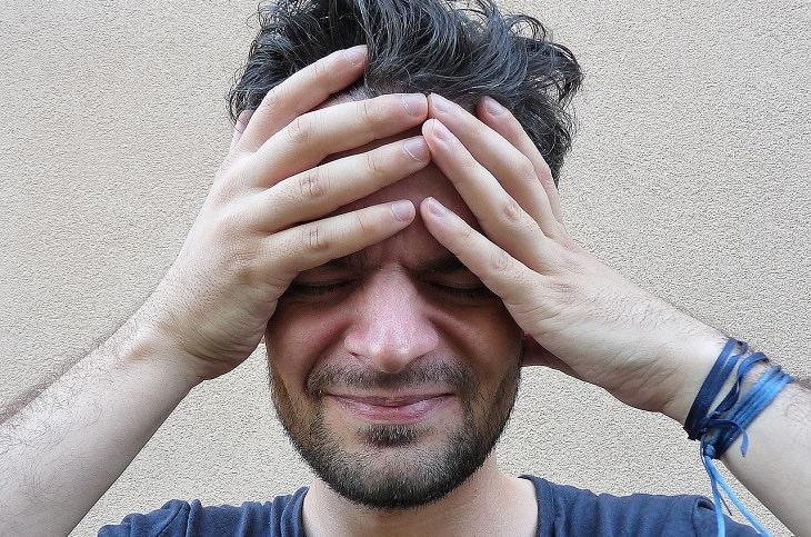 גבר שאוחז בראשו בכאב