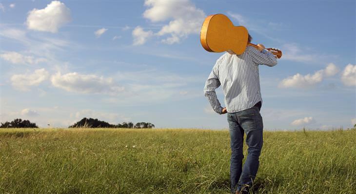 איש עומד בשדה ירוק רחב ידיים ומחזיק גיטרה על כתפו