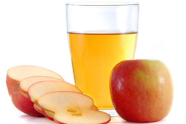 תפוחים ליד כוס עם חומץ תפוחים