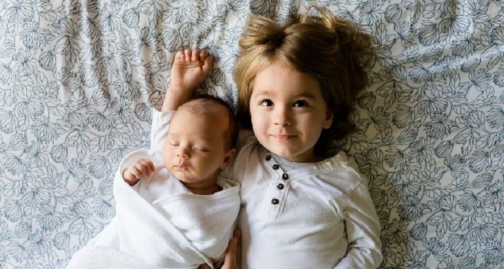 ילדה שוכבת על מיטה ואוחזת באחיה התינוק