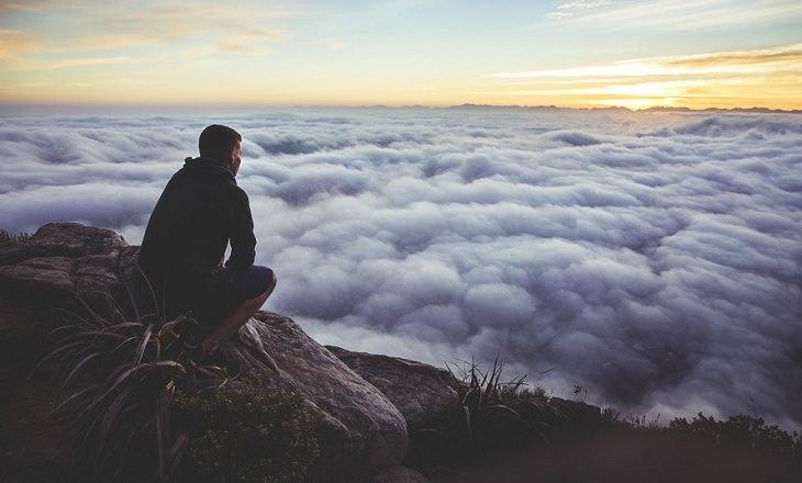 אדם על פסגת הר צופה על מעל העננים
