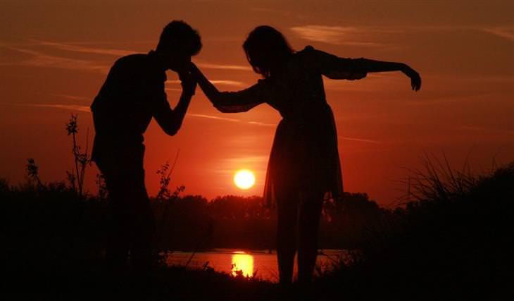 צללית של גבר מנשק את ידה של אישה על רקע שקיעת השמש