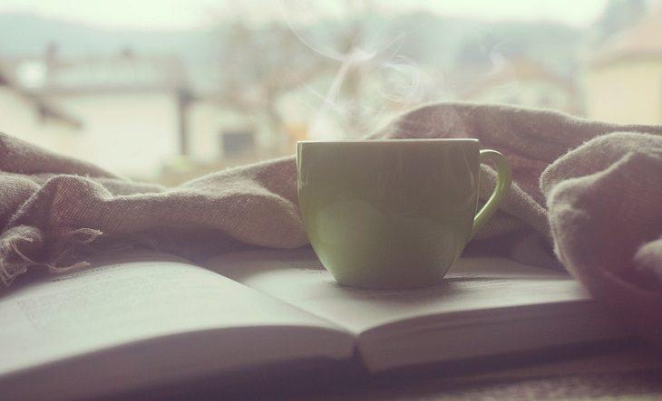 כוס קפה מהביל מונחת על ספר