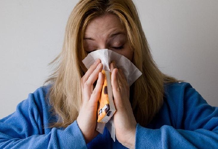 אישה לבושה בחלוק ומקנחת את האף