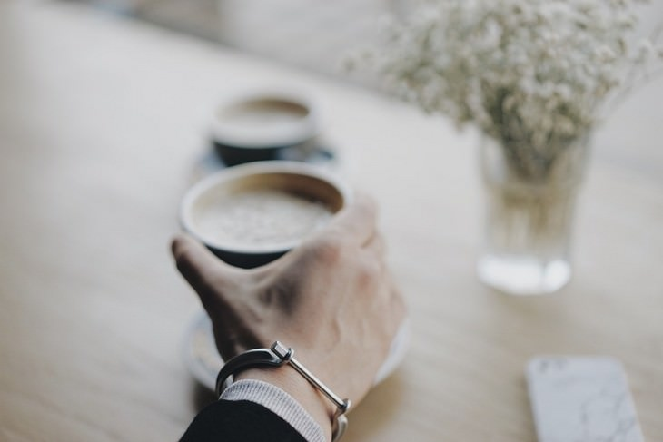 יד של גבר אוחזת בכוס קפה