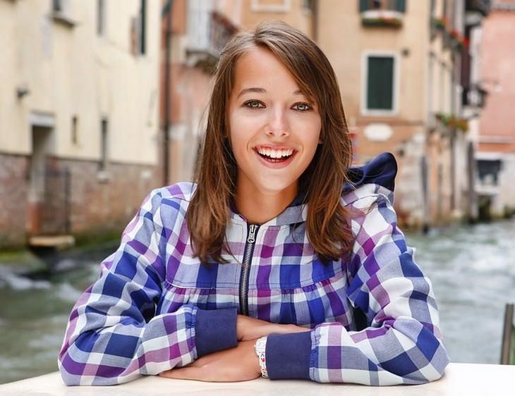 אישה צעירה מחייכת חיוך רחב