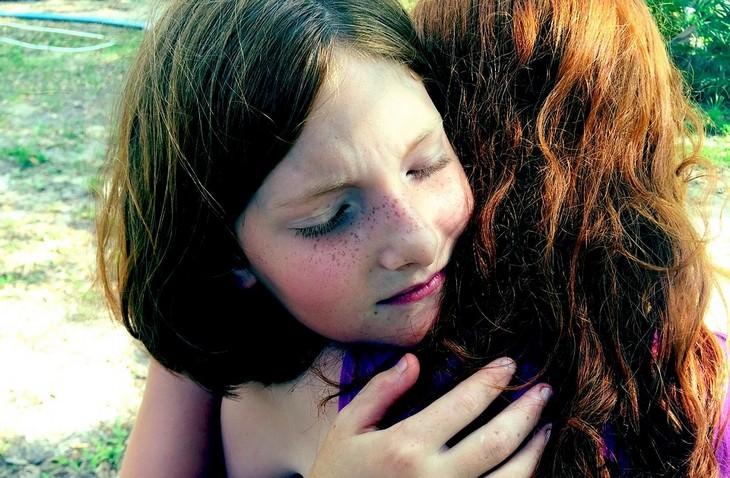 ילדה אדמונית מחבקת את אימה בעיניים עצומות