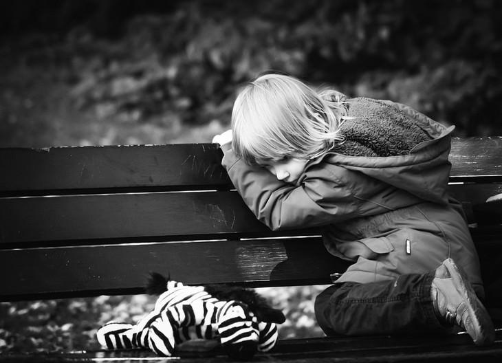 ילד עצוב יושב שעון על ספסל עם בובת זברה לצידו