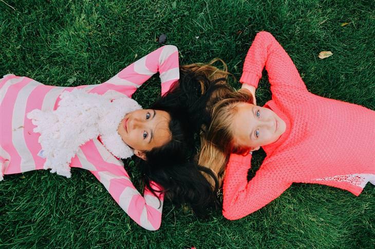 שתי ילדות שוכבות על הדשא, ראש לראש