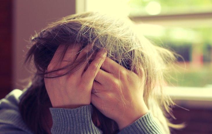 אישה מניחה את ידיה על ראשה בייאוש