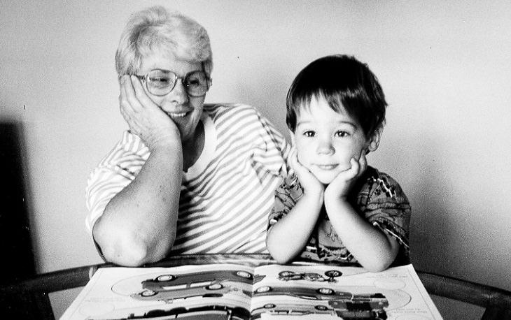 סבתא מסתכלת על הנכד שלה, שיושב מול ספר