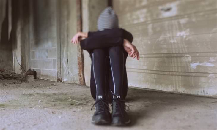 אישה יושבת על הרצפה עם ברכיים מכופפות וראשה מונח בתוך ידיה