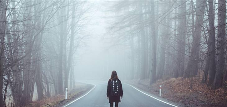 אישה עומדת על כביש שעובר בתוך יער אפלולי
