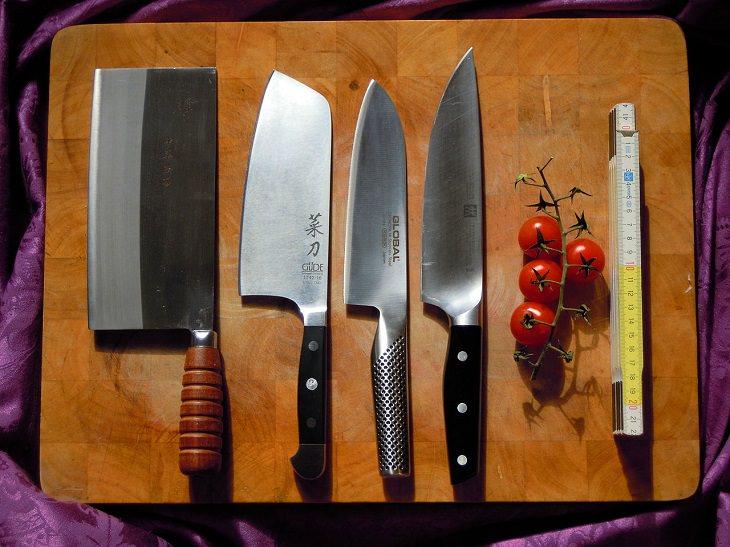 סכיני שף מונחות על קרש עץ