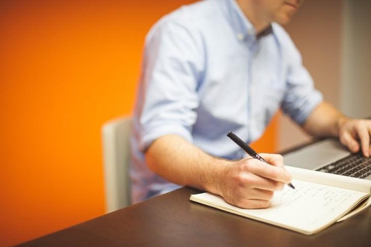 איש כותב במחברת לצד מחשב נייד