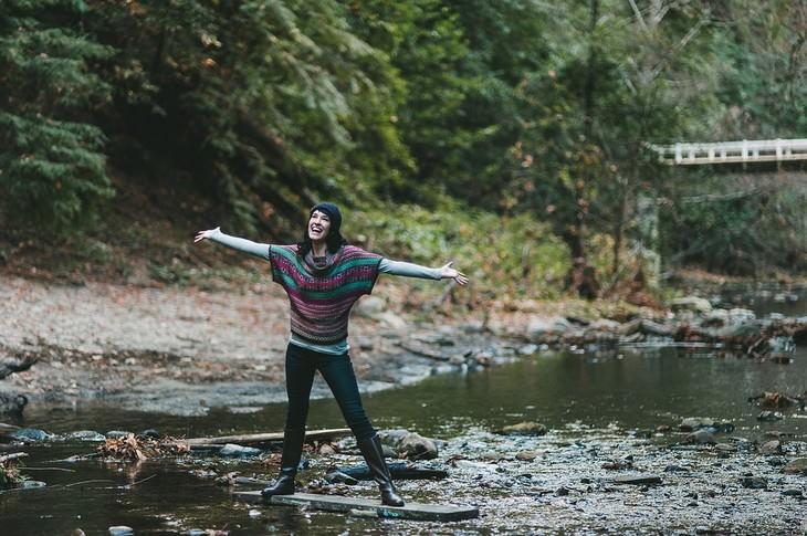 אישה עומדת באמצע נהר ומחייכת